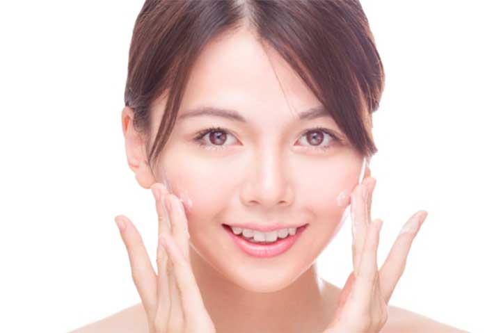 Asian beauty applying cream to face