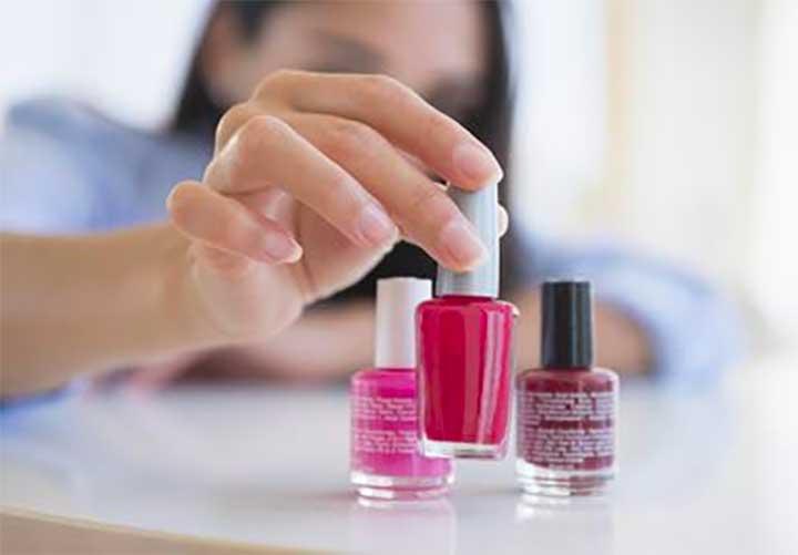 Caucasian woman selecting bottle of nail polish