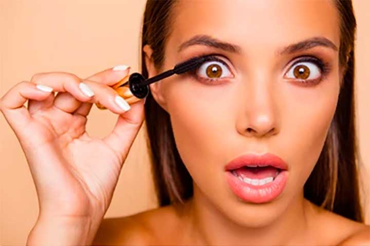 Woman Applying Mascara Mouth Open Curlers In Hair