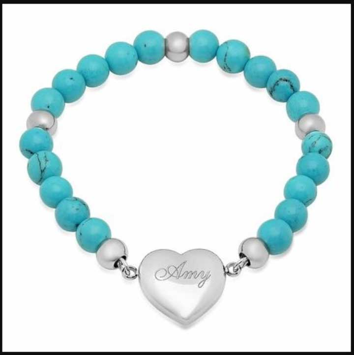 A heart charm bracelet with an engraving